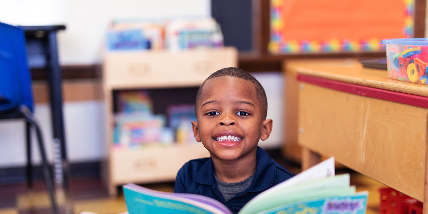 Smiling student reading a book in a classroom.