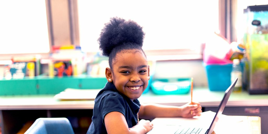 Smiling student sitting at desk in a classroom.